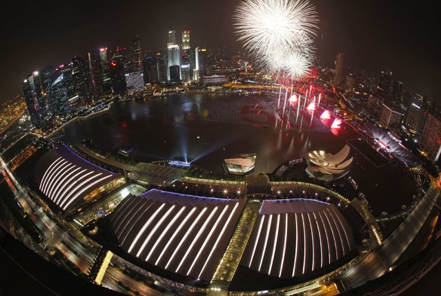 Fireworks light up the sky from a floating installation of 25,000 wishing spheres lining the Marina Bay in the backdrop of the city's financial district during the New Year's Day countdown celebrations in Singapore January 1, 2015. People penned their New Year wishes on these spheres throughout December to be placed in the waters as part of the New Year Day celebrations, marking the city-state's 50th year of independence. (Photo by Edgar Su/Reuters)