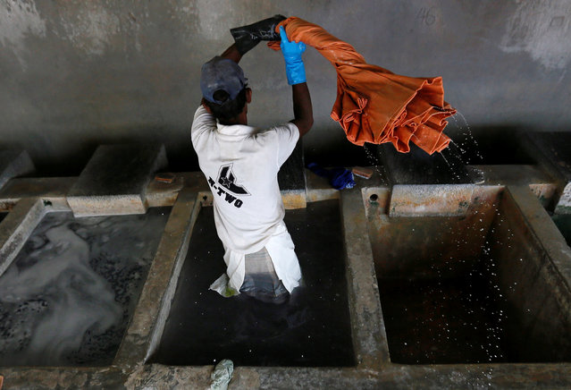 A man washes cloths in a water tank at a laundry in Colombo, Sri Lanka, October 7, 2016. (Photo by Dinuka Liyanawatte/Reuters)