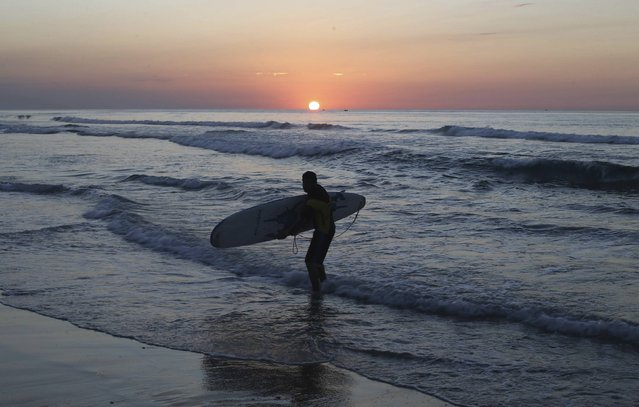 A Palestinian man carries a surfboard during sunset in the Mediterranean sea off the coast of Gaza City December 31, 2014. (Photo by Ibraheem Abu Mustafa/Reuters)
