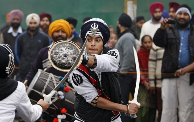 Indian Sikh warriors display traditional martial art skills during a religious procession ahead of the birth anniversary of Guru Gobind Singh in Jammu, India, Monday, January 5, 2015. The birth anniversary of Guru Gobind Singh, the tenth Sikh guru, will be marked on Jan. 7 this year. (Photo by Channi Anand/AP Photo)