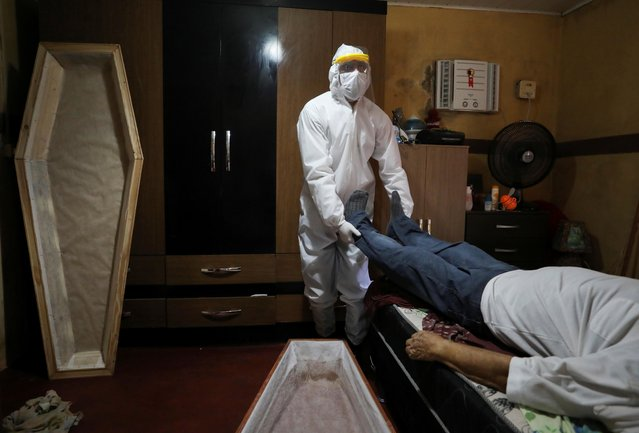 A worker of the Funeral SOS, wearing protective clothing, prepares to remove the body of Antonio Freitas, at his house, amid the coronavirus disease (COVID-19) outbreak, at Tancredo Neves neighborhood in Manaus, Brazil on May 7, 2020. (Photo by Bruno Kelly/Reuters)