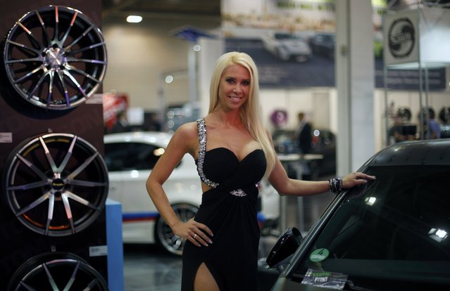 A model poses between car rims and a tuned car at the Essen Motor Show in Essen, Germany, November 27, 2015. (Photo by Ina Fassbender/Reuters)