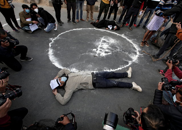 Protesters lie down on the road next to the Nepalese word that means parliament during a protest against the dissolution of parliament, in Kathmandu, Nepal on January 15, 2021. (Photo by Navesh Chitrakar/Reuters)