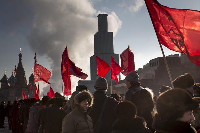 Russian Communist supporters hold Soviet Red flags as they prepare to visit the Mausoleum for the 91st anniversary of Lenin's death at Moscow's Red Square with St. Basil Cathedral, left, the Kremlin's Spassky Tower, center, in Moscow, Russia, Wednesday, January 21, 2015. The Spassky Tower is closed for a restoration. (Photo by Alexander Zemlianichenko/AP Photo)