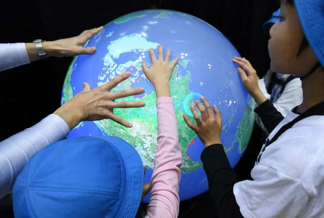 Schoolchildren touch an electronic globe to learn the rise in sea levels by global warming during the Eco Products exhibition in Tokyo on December 10, 2015. Some 700 private companies, local governments, NGOs, universities and institutes took part in the annual three-day exhibition. (Photo by Toru Yamanaka/AFP Photo)