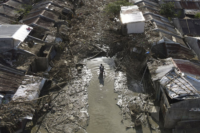 Two residents walk along a path of mud and debris towards their village damaged by Typhoon Vamco in Rodriguez, Rizal province, Philippines on Tuesday, November 17, 2020. Typhoon Vamco left dozens of people dead as it swelled rivers and flooded low-lying areas while it passed over the capital and storm-battered northeast Philippines. (Photo by Aaron Favila/AP Photo)