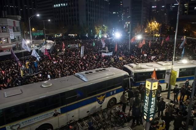 Protesters gather between a cordon of police buses during an anti-government protest in the Gwanghwamun area of central Seoul on November 12, 2016. Up to one million people were expected to take to the streets of Seoul to demand the resignation of scandal-hit President Park Geun-Hye, in one of the largest anti-government protests in decades. (Photo by Ed Jones/AFP Photo)