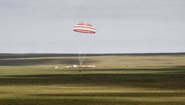 The return capsule of the Shenzhou-10 spacecraft lands in the grasslands of north China's Inner Mongolia region, on June 26, 2013, following a 15-day mission in space. (Photo by AFP Photo via The Atlantic)