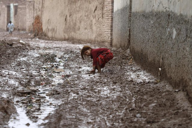A girl reacts to camera as she bends to recover her pair of shoe from mud after the rain on outskirts of Peshawar January 22, 2015. (Photo by Fayaz Aziz/Reuters)