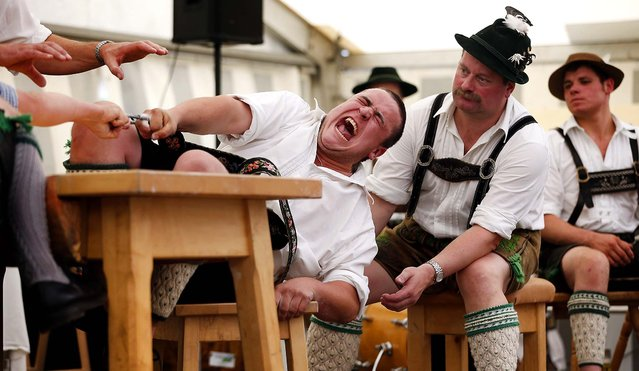 A man tries to pull his opponent over the table during the Alps Finger Wrestling championships in Mittenwald, Germany, on July 7, 2013. (Photo by Matthias Schrader/Associated Press)
