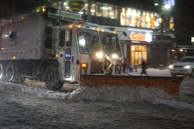 A snow plow clears the road down Lexington Avenue near Grand Central Terminal as it snows in the Manhattan borough of New York January 26, 2015. (Photo by Carlo Allegri/Reuters)