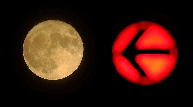 A red traffic light is seen next to the moon in downtown Frankfurt, Germany November 14, 2016. (Photo by Kai Pfaffenbach/Reuters)