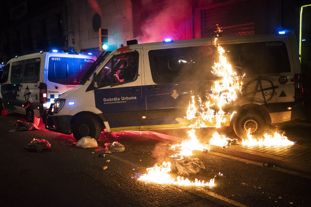 A police van is set on fire as protestors throw molotov cocktails at police during clashes following a protest condemning the arrest of rap singer Pablo Hasél in Barcelona, Spain, Saturday, February 27, 2021. (Photo by Emilio Morenatti/AP Photo)