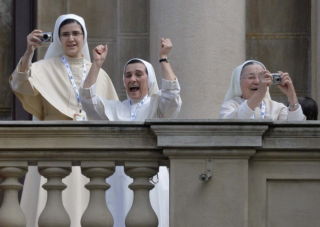 Nuns celebrate and take pictures as Pope Francis arrives to give the Angelus noon prayer in Rio de Janeiro on July 26, 2013. (Photo by Luca Zennaro/Associated Press)