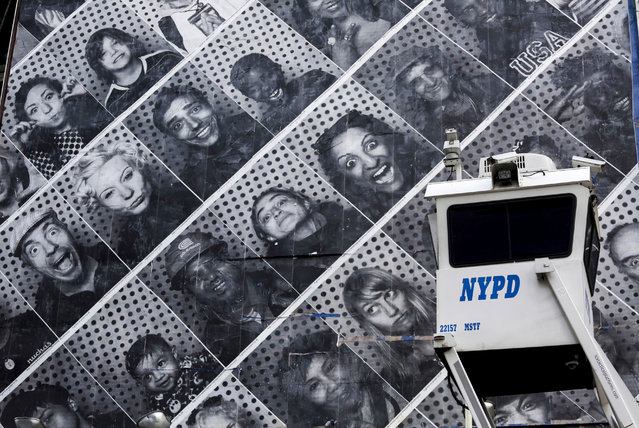 A New York Police Department SkyWatch observation tower is stationed in midtown Manhattan, Wednesday, July 31, 2013 in New York. Behind it is a billboard filled with people's photographs. The towers, equipped with cameras and sometimes a police officer, are deployed in known high crime areas. (Photo by Mark Lennihan/AP Photo)
