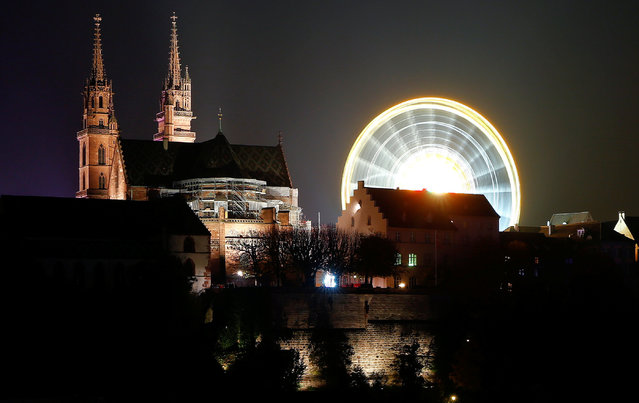 A long time exposure shows a ferris wheel turning beside the Muenster church during the annual Herbstmesse fair in Basel, Switzerland October 29, 2016. (Photo by Arnd Wiegmann/Reuters)