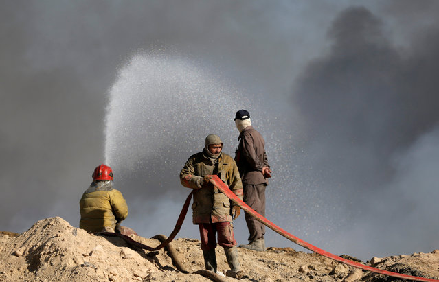Oil workers work in front of oilfields burned by Islamic State fighters in Qayyara, south of Mosul, Iraq November 23, 2016. (Photo by Goran Tomasevic/Reuters)
