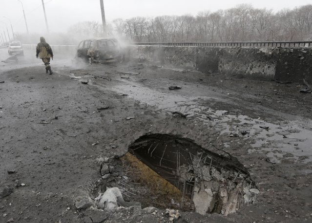 A Pro-Russian rebel walks past a car destroyed by a rocket during recent shelling in Donetsk, Ukraine, Monday, February 9, 2015. An armed conflict between Russia-backed separatists and Ukraine government forces has killed more than 5,300 people and displaced more than a million people in eastern Ukraine. (Photo by Petr David Josek/AP Photo)