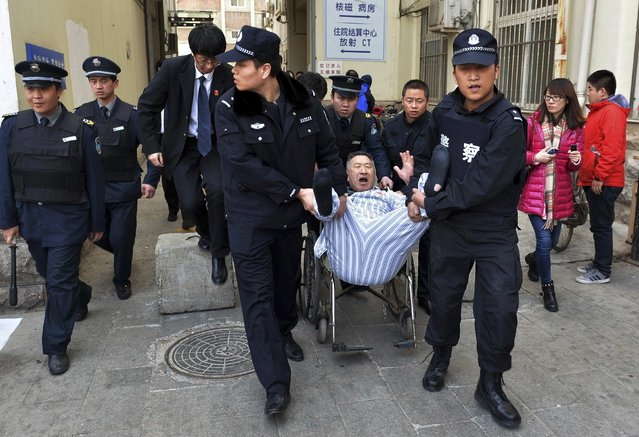 Police officers carry a man (C) out of a hospital as they enforce a court order in Beijing February 10, 2015.  The man, 55, surnamed Chen, received treatment at the hospital after a traffic accident in August 2011. Chen returned to the hospital two months later, saying he had pains in his left leg and as a protest, he refused to be discharged even though the hospital stopped providing any further treatment in July 2012. (Photo by Reuters/Stringer)