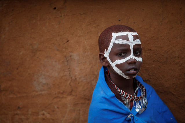 A Maasai boy with a painted face looks at the camera during an initiation into an age group ceremony near the town of Bisil, Kajiado county, Kenya on August 23, 2018. (Photo by Baz Ratner/Reuters)