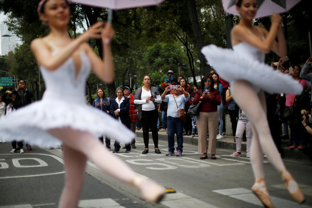 "Spectators look at the classical ballet company ""Ardentia"" as they perform in the streets of Mexico City on traffic lights, in an effort to highlight the city's fine arts in public spaces in Mexico, September 8, 2018. (Photo by Carlos Jasso/Reuters)"