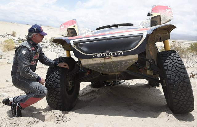 Carlos Sainz of Spain kneels down next to his Peugeot after it broke down during the 10th stage of the Dakar Rally 2016 near Fiambala, Argentina, January 13, 2016. (Photo by Franck Fife/Reuters)