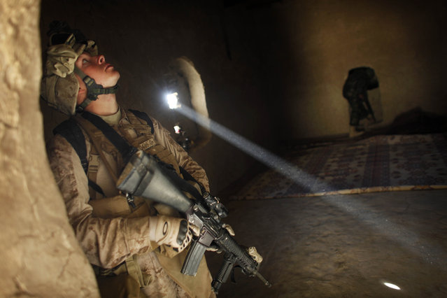 """United States Marine LCpl. Franklin Romans of Michigan, from the 2nd Battalion 2nd Marines """"Warlords"""" searches a house during an operation in the Garmsir district of the volatile Helmand province, southern Afghanistan, on December 23, 2009. (Photo by Kevin Frayer/AP Photo/File)"""