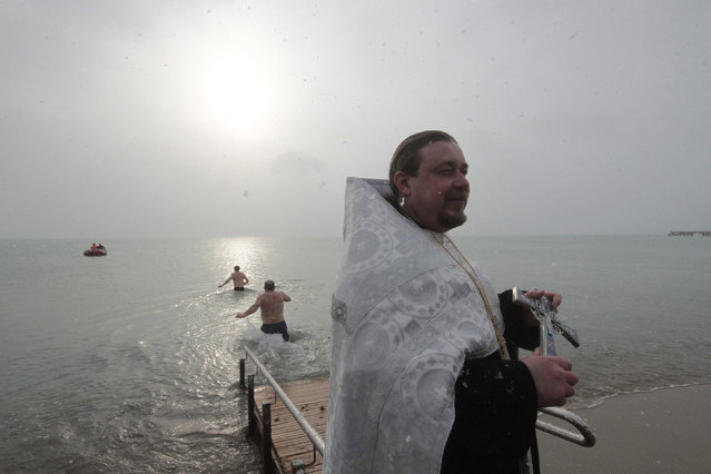 Orthodox priest holds a cross as people take a dip in cold waters of the Black Sea during Orthodox Epiphany celebrations in the port city of Yevpatoriya, Crimea, January 19, 2016. (Photo by Pavel Rebrov/Reuters)