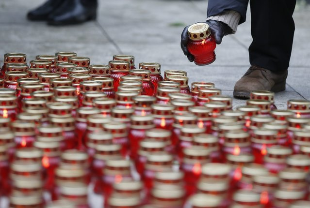 People place lit candles on the ground as they gather to attend a memorial service before the funeral of Russian leading opposition figure Boris Nemtsov in Moscow, March 3, 2015. Several hundred Russians, many carrying red carnations, queued on Tuesday to pay their respects to Boris Nemtsov, the Kremlin critic whose murder last week showed the hazards of speaking out against Russian President Vladimir Putin. REUTERS/Maxim Shemetov