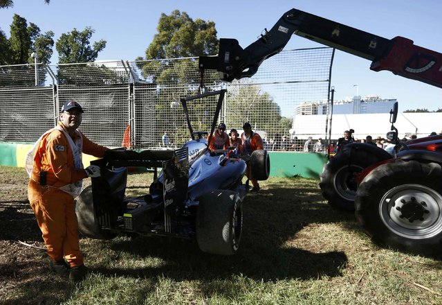 Course officials load the car of McLaren Formula One driver Kevin Magnussen of Denmark onto a recovery vehicle after he crashed during the second practice session of the Australian F1 Grand Prix at the Albert Park circuit in Melbourne March 13, 2015.  REUTERS/Jason Reed