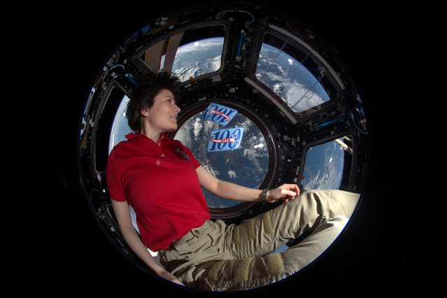"""Italian ESA astronaut Samantha Cristoforetti poses in the Cupola module of the International Space Station with two 100-day patches to mark her 200th day in space on June 10, 2015. Samantha first flew to the International Space Station on a Soyuz spacecraft in 2014 for a mission known as """"Futura"""". (Photo by ESA/NASA)"""