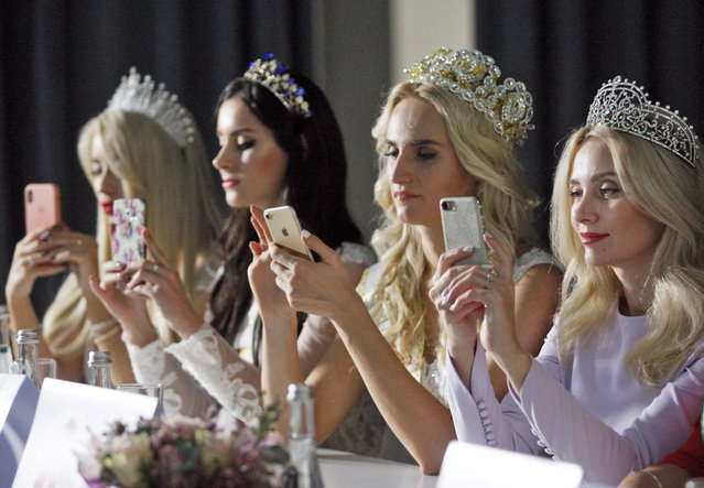 """The jury members use mobile phones during the """"Miss Ukraine Plus Size"""" beauty pageant in Kiev, Ukraine on October 29, 2018. (Photo by Pavlo Gonchar/SOPA Images via ZUMA Wire)"""