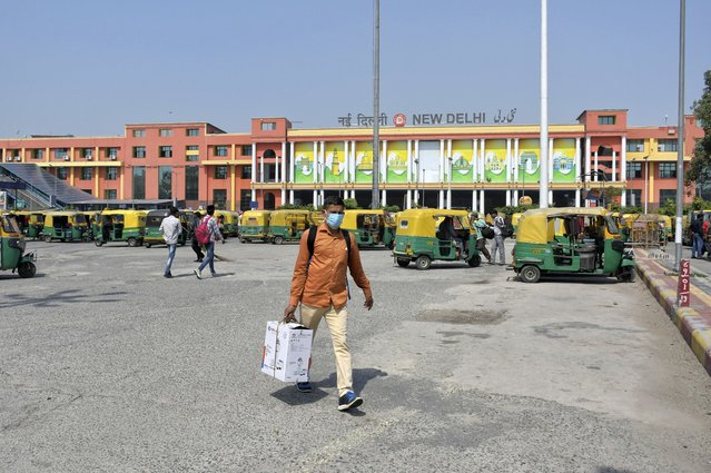 Passengers walk outside the New Delhi railway station in New Delhi, India, Monday, June 7, 2021. (Photo by Ishant Chauhan/AP Photo)