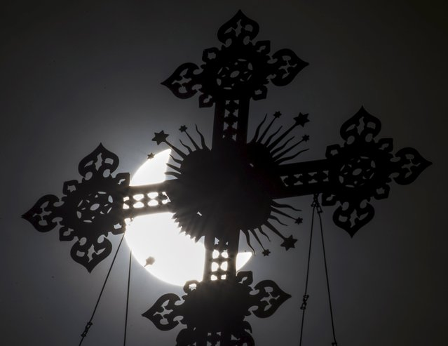 A cross on the dome of the Cathedral of Christ the Saviour is seen during a partial solar eclipse in Moscow, March 20, 2015.  A solar eclipse thrilled thousands of sky gazers on remote Arctic islands on Friday but clouds disappointed some viewers of a rare celestial show that was also partly visible for millions in Europe, Africa and Asia. (Photo by Maxim Shemetov/Reuters)