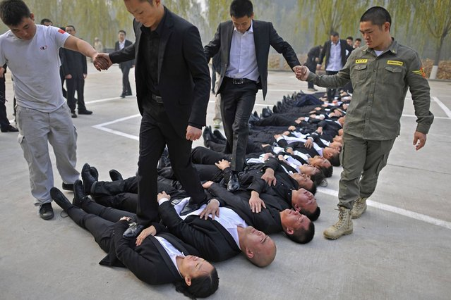 Trainees walk over the bodies of their fellow trainees during the Tianjiao Special Guard/Security Consultant Ltd. bodyguard training camp in Beijing, China, on November 5, 2013. (Photo by Reuters)