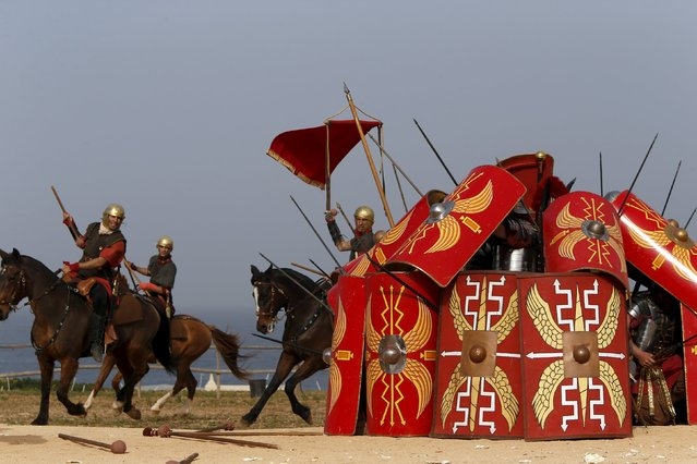 Members of the Legio X Fretensis (Malta) re-enactment group demonstrate a defensive formation while under cavalry attack during a display of ancient Roman army life at Fort Rinella in Kalkara, outside Valletta, March 22, 2015. (Photo by Darrin Zammit Lupi/Reuters)