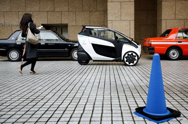 A Toyota i-Road electric vehicle (C) parks outside a hotel in Tokyo April 9, 2015. (Photo by Thomas Peter/Reuters)