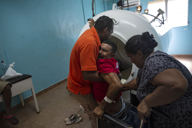 """In this February 9, 2018 photo, paralyzed by decompression sickness, lobster diver Misael Banegas Diaz, 49, is lifted by physical therapist Cedrak Waldan Mendoza into a hyperbaric chamber at the hospital in Puerto Lempira, Honduras. Waldan Mendoza said the divers are driven by poverty, and even if injured, they return to the boats. """"You run into them in the street and ask them why they're going (back to diving) and they say it's because their kids are hungry"""". (Photo by Rodrigo Abd/AP Photo)"""