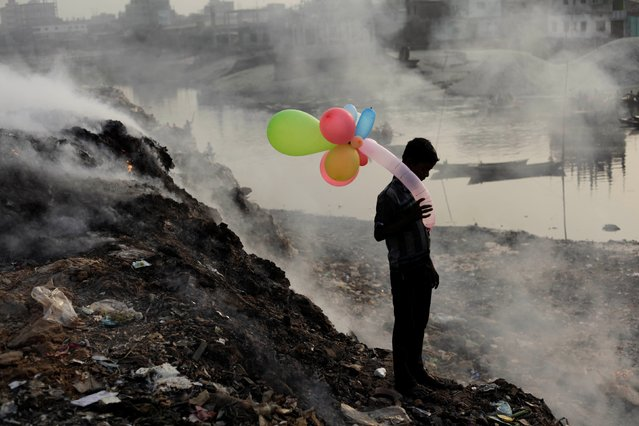 """""""Honorable Mention"""". A boy plays with balloons by Buriganga river as smoke emits from a dump yard during sunset in Dhaka, Bangladesh. Photo location: Dhaka, Bangladesh. (Photo and caption by Andrew Biraj/National Geographic Photo Contest)"""