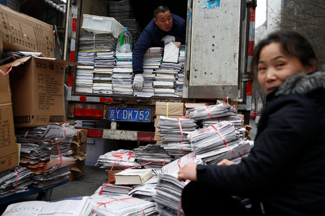 People sort old newspapers and books for recycling in a street in Beijing, China January 5, 2017. (Photo by Thomas Peter/Reuters)