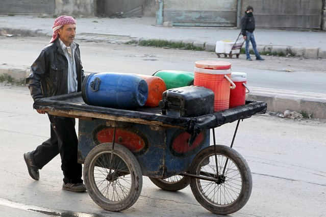 A man pushes a cart with water containers in Bab Neirab, Aleppo, Syria February 15, 2016. (Photo by Abdalrhman Ismail/Reuters)