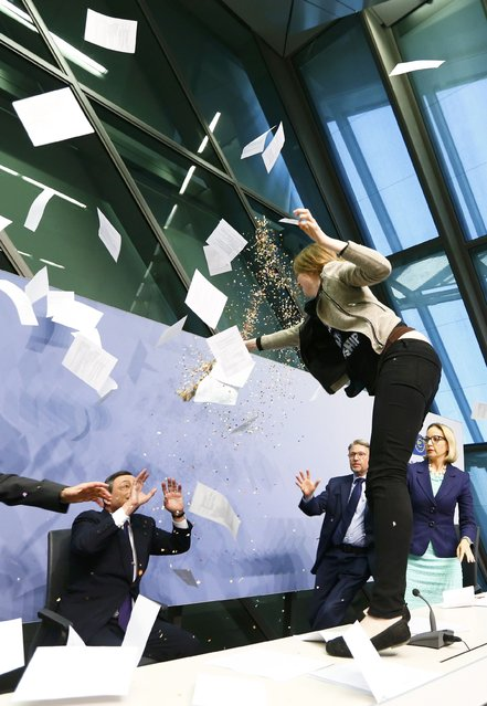 A protester jumps on the table in front of the European Central Bank President Mario Draghi (L) during a news conference in Frankfurt, April 15, 2015. (Photo by Ralph Orlowski/Reuters)