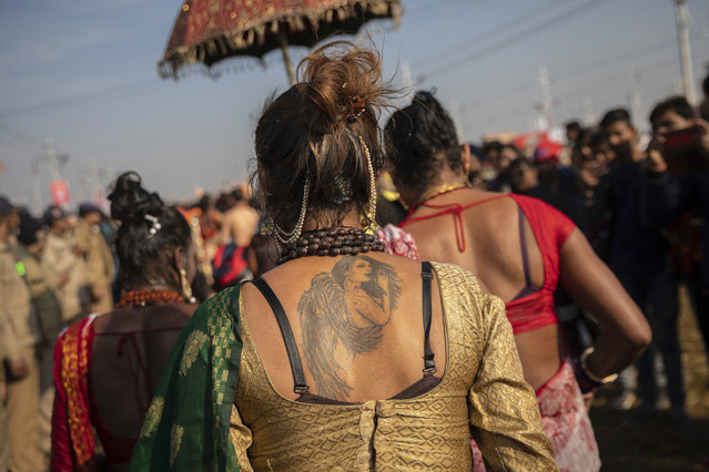 """In this January 15, 2019, photo, Indian hijras of the """"Kinnar akhara"""" monastic order leave the river bank after taking a dip on the auspicious Makar Sankranti day during the Kumbh Mela festival in Prayagraj, Uttar Pradesh state, India. Unlike other akharas, which are only open to Hindu men, Kinnar, founded in 2015, is open to all genders and religions. Hinduism's ancient Vedas scriptures describe transgender people, or hijras, as holding an integral space in society. (Photo by Bernat Armangue/AP Photo)"""
