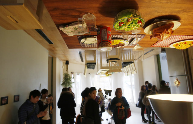 Visitors look around inside an upside-down house created by a group of Taiwanese architects at the Huashan Creative Park in Taipei, Taiwan, Tuesday, February 23, 2016. (Photo by Wally Santana/AP Photo)
