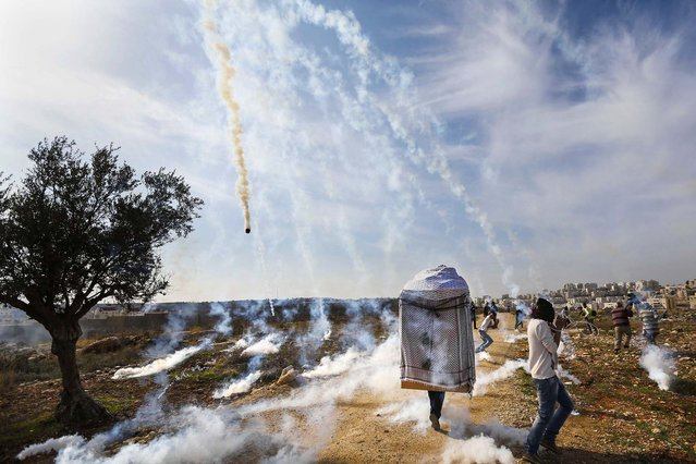 A man wearing a large puppet head and Palestinian stone-throwing protesters run as tear gas is fired by Israeli soldiers during clashes at a weekly demonstration against Jewish settlements in the West Bank village of Bilin, near Ramallah, on January 3, 2013. (Photo by Mohamad Torokman/Reuters)