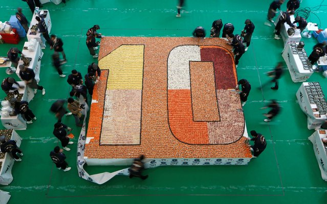 Staff members from a Japanese sushi chain restaurant remove a banner after creating a sushi mosaic to mark the 10th anniversary of the restaurant at a shopping mall in Hong Kong Wednesday, January 8, 2014. A total of 20,647 pieces of sushi were formed into a 37.16-square-meter (400-square-foot) space which broke the Guinness World Records of the largest sushi mosaic. (Photo by Kin Cheung/AP Photo)