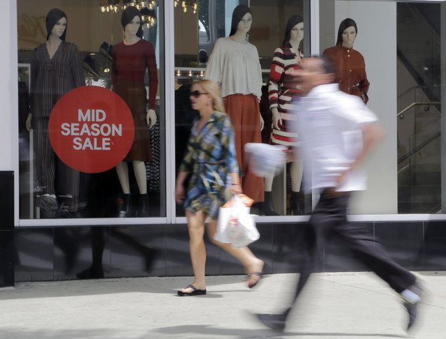 In this March 13, 2015 photo, pedestrians walk past a sign advertising a sale at H&M along Lincoln Road Mall in Miami Beach, Fla. (Photo by Lynne Sladky/AP Photo)