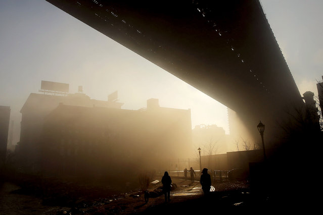 People walk on a Brooklyn promenade under the Manhattan Bridge on a morning with dense fog on January 15, 2014 in New York City. (Photo by Spencer Platt/Getty Images)