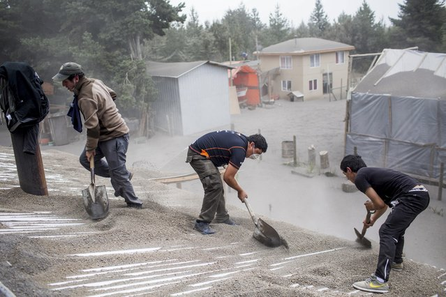 Men remove ash from a building's roof, left by the Calbuco volcano, in Ensenada, Chile, Thursday, April 23, 2015. (Photo by Pablo Sanhueza Gutierrez/AP Photo)