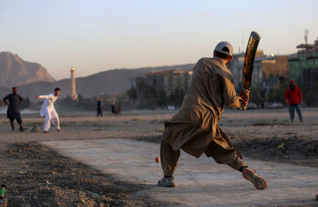 Men play cricket in Kabul, Afghanistan, 16 September 2021. A humanitarian crisis and alleged widespread human rights violations are among the top challenges Afghanistan faces a month after the Taliban's lightning-fast capture of Kabul. The economic crisis threatened to push 97 percent of the 40 million people into poverty by mid-2022, the United Nations has warned. (Photo by EPA/EFE/Stringer)